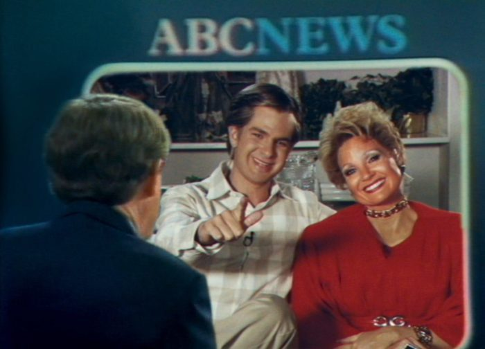 A television screen shows a couple talking to an interviewer.