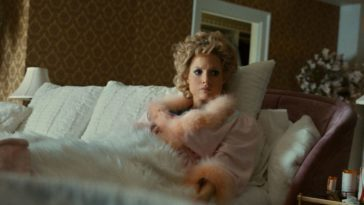 Tammy Faye rolls over in bed towards her talking husband.