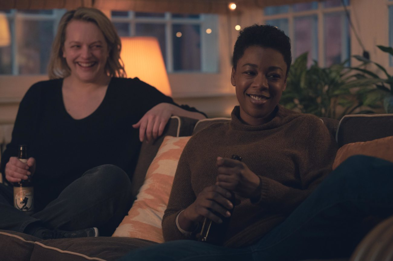 June and Moira sit on a couch together, happy