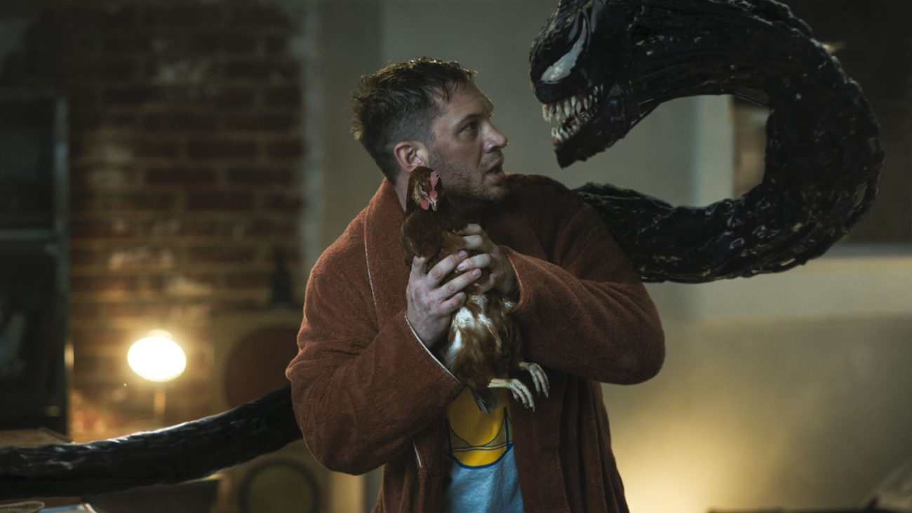 Eddie talks to his attached symbiote while holding a chicken.