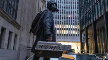 Yorick, in full black hazmat suit and gas mask, carries a pet carrier through a city street and looks up at the sky