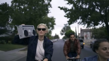 Members of Dead Sara ride bikes through suburban streets. Emily Armstrong is holding a boom box.