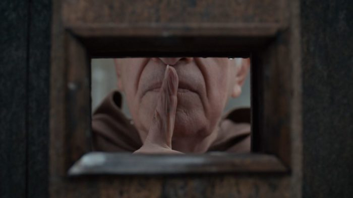 A man holds a finger to his lips, signifying silence.