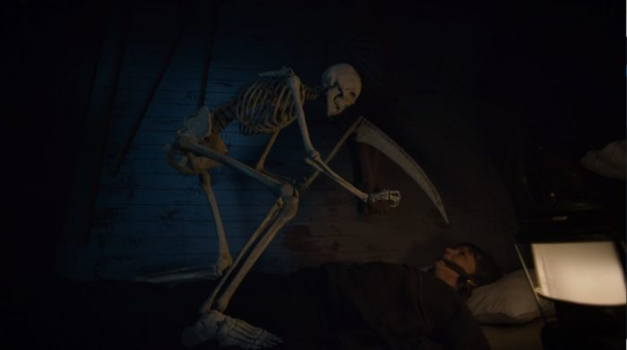 An animated skeleton statue reaches for Kristen.