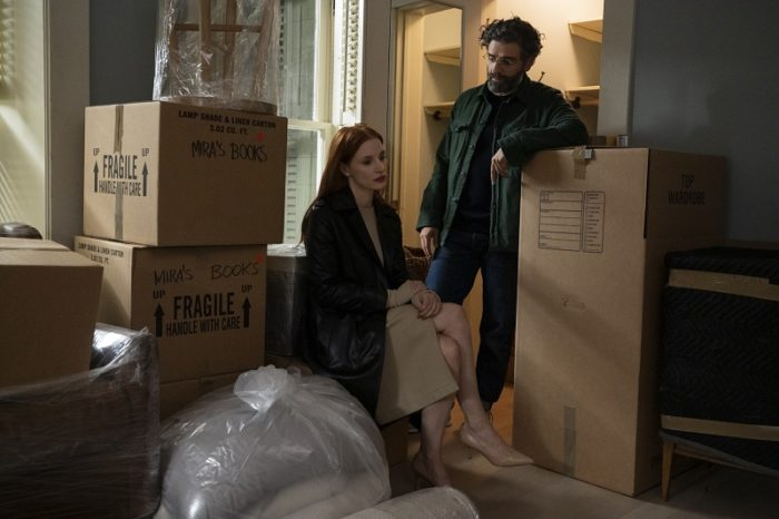 Mira (Jessica Chastain) sits and Jonathan (Oscar Isaac) stands, leaning on a packing box amid many in their house. a house full of packed boxes.