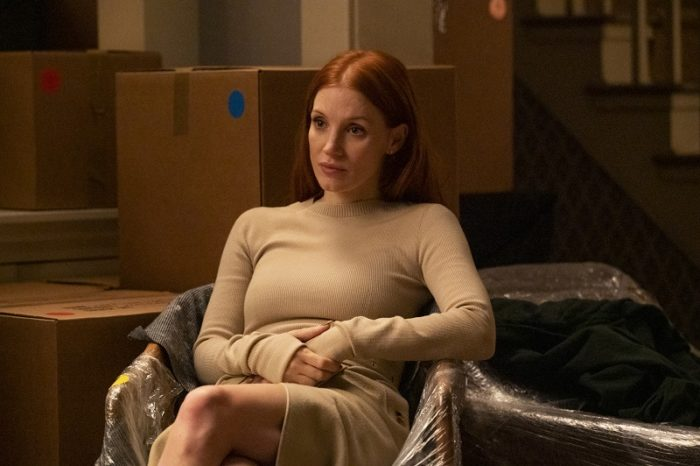 Mira (Jessica Chastain) sits on a wrapped sofa in front of packing boxes, looking pensively to her left.