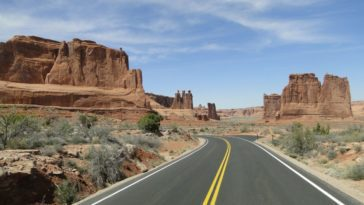 A road wanders through the buttes and mesas of the American southwest.