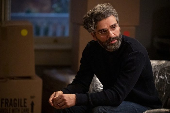 Jonathan (Oscar Isaac) is depicted wearing a black turtleneck and looking to his left, seated on a wrapped sofa.