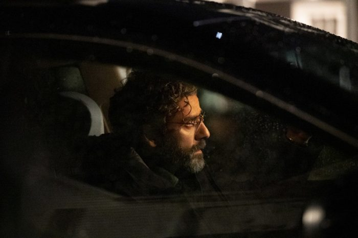 Jonathan (Oscar Isaac) is depicted behind the wheel of his car, looking back into his rear-view mirror as he slowly drives away.