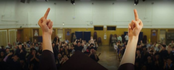 Two middle fingers (Abbi's) raised into the air, as seen from behind facing an assembly of students
