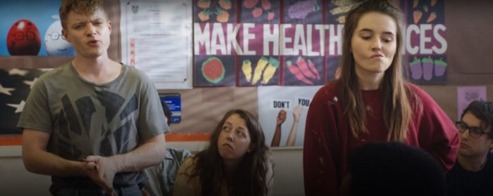 Abbi makes a face while Caleb talks as the two stand in a classroom