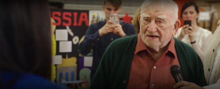 """Mr. Holmes (Ed Asner) talks into a microphone as students stand behind him taking pictures with their phones in The Premise, """"The Ballad of Jesse Wheeler"""""""