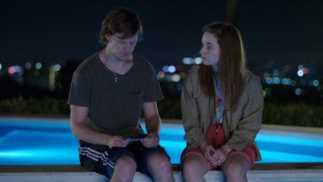 Abbi and Jesse Wheeler sit by a pool as he looks at a photo in his hands in The Premise S1E3