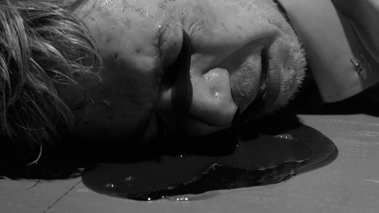Black oil spills from the eyes and nose of a man lying on the ground