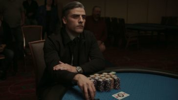 A gambler covets his stacks of chips at a card table.
