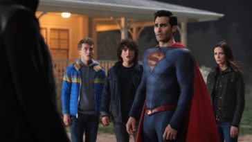 Superman stands between a villain in front of him and his family behind him near their rural home's porch.