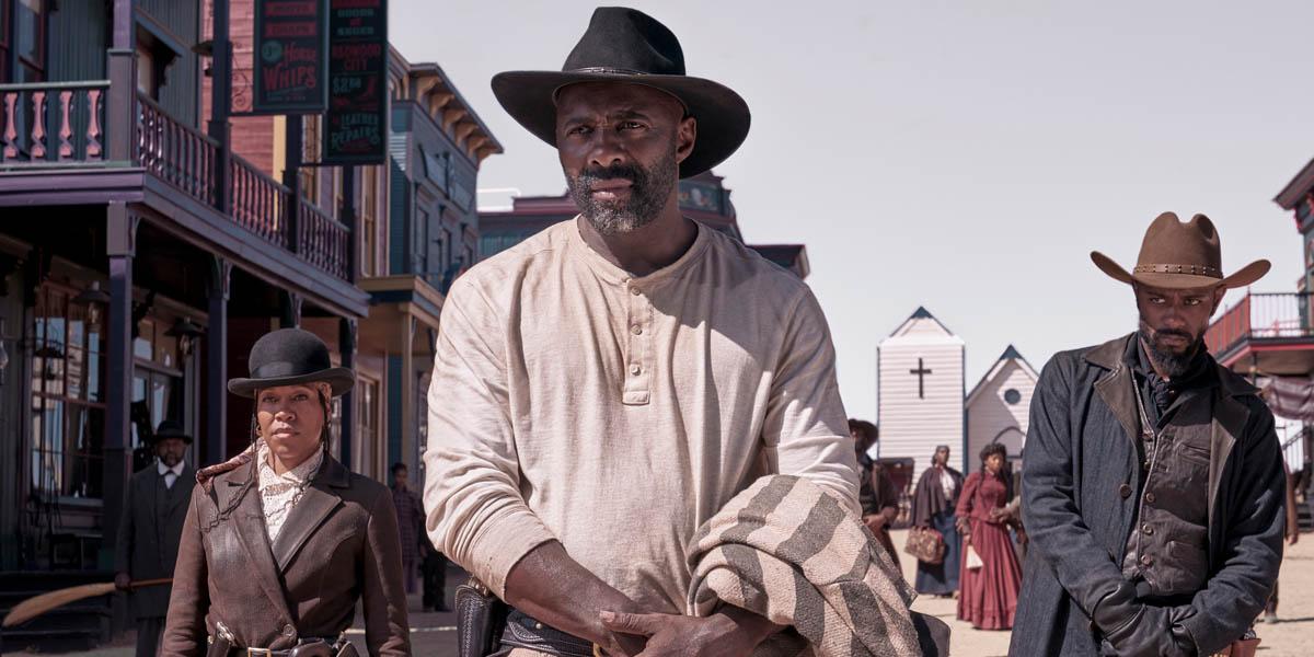 A Black cowboy leads a group on horseback through a town.