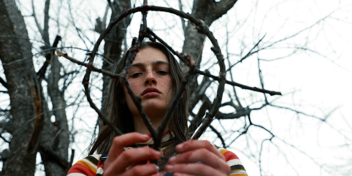 A teen girl forms a symbol out of sticks.