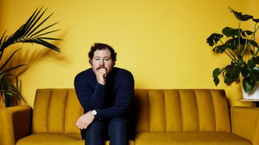 David James Allen sits on a dark yellow couch in a yellow painted room