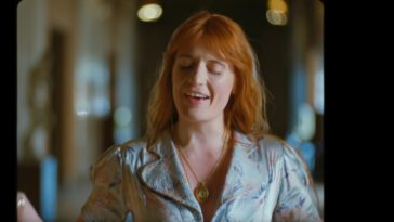 """Florence Welch closes her eyes as she stands in a hallway and sings in the music video for """"Hunger"""" by Florence + The Machine"""