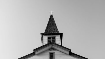 A church steeple rises into an overcast sky as seen from a low angle.