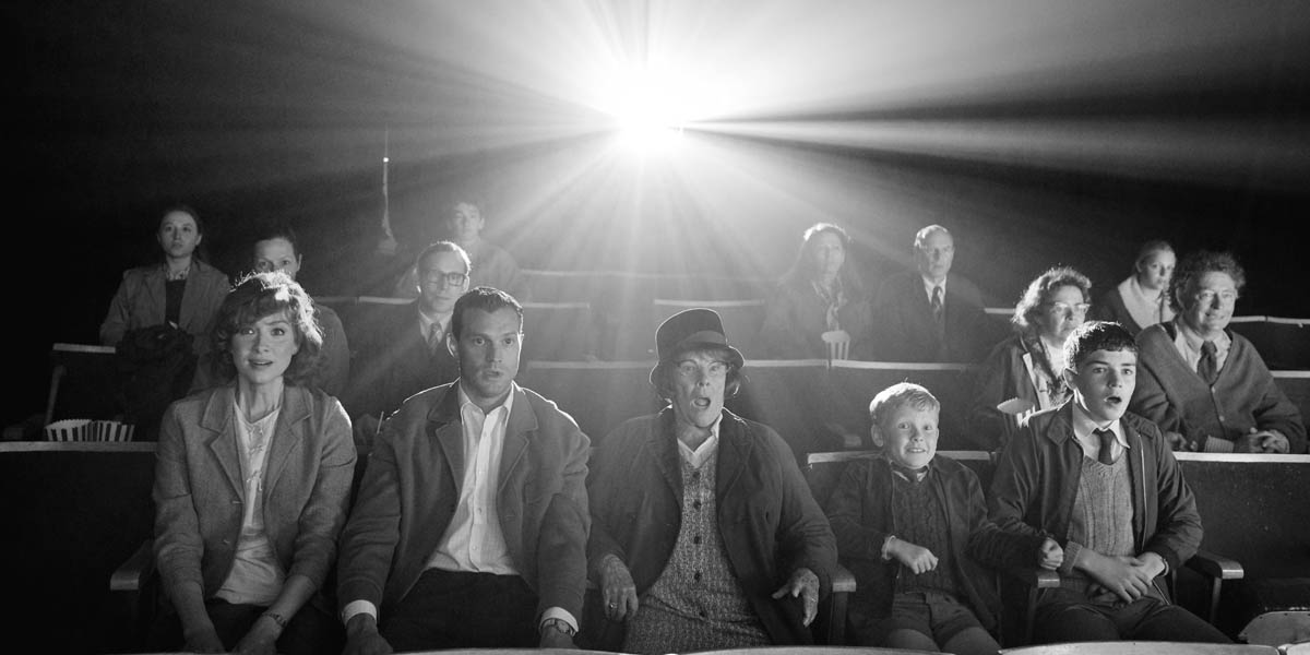 A small gathering watches a cinema showing.