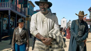 A man stands armed in a street and backed by two fellow outlaws.