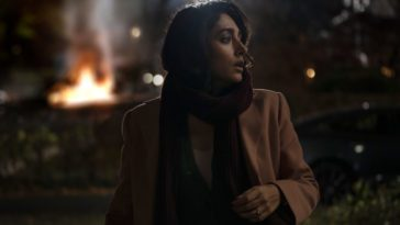Aneesha looks back over her shoulder, as cars burn in the background