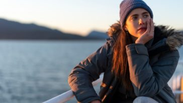In this image from Maid, Alex (Margaret Qualley) is depicted on a ferry, wearing a winter jacket and knit cap, looking pensively off screen with the shore in the background.