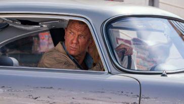 James Bond looks out his damaged car towards his pursuers.