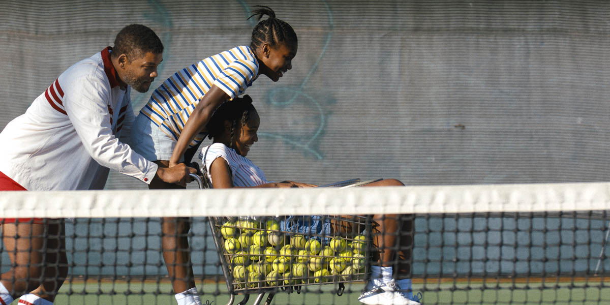 A man pushes a tennis ball cart with two girls.