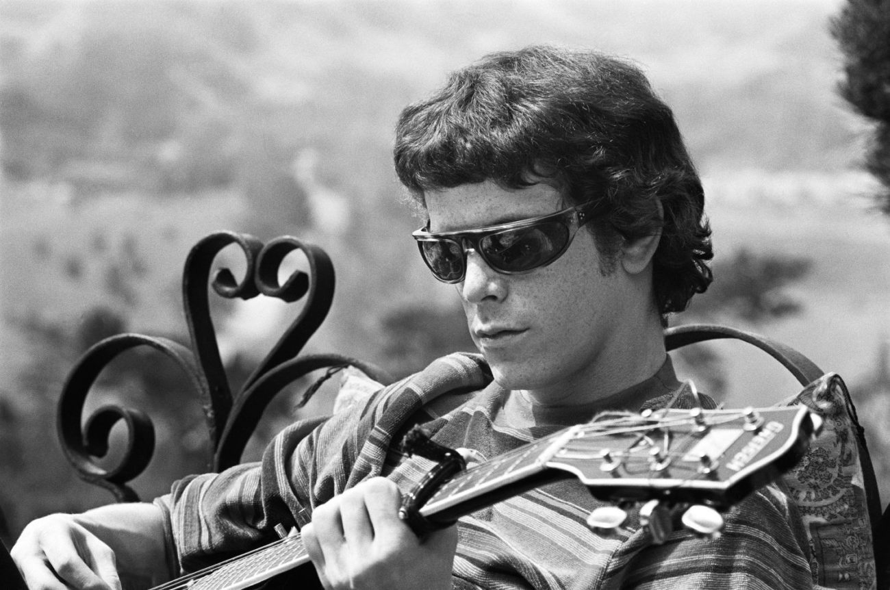 A man in sunglasses is playing a guitar.