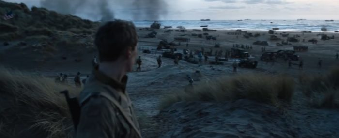A soldier stands on a beach where troops are marching in Operation Mincemeat