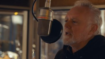 """Roger Taylor sings in a recording studio in the music video for """"We're All Just Trying to Get By"""""""