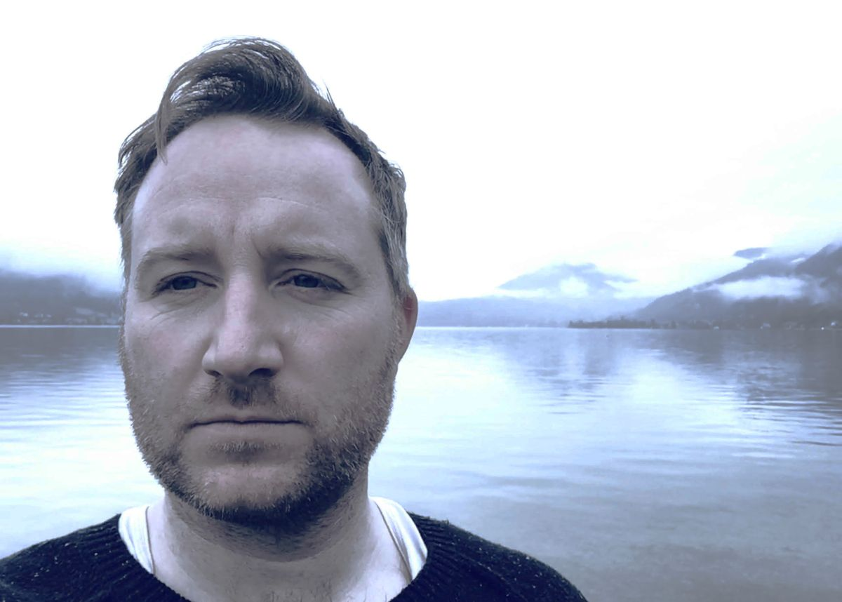 Composer Ross Power stands at a white cold body of water in London