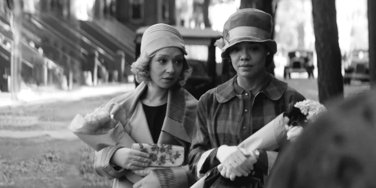 Two women in hats meet on the street.