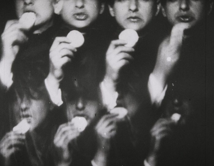 Still from the 1932 short film Europa as exhibited at the Tate gallery: rows of faces consuming slices of apple