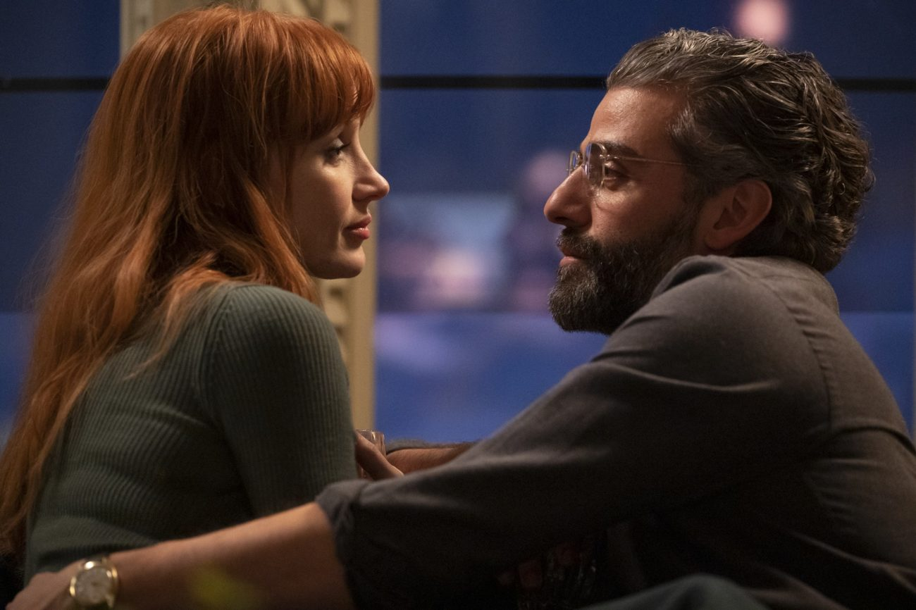 In this image from Scenes from a Marriage Episode 5, MIra (Jessica Chastain) and Oscar Isaac) embrace while seated on a sofa and looking directly at one another.