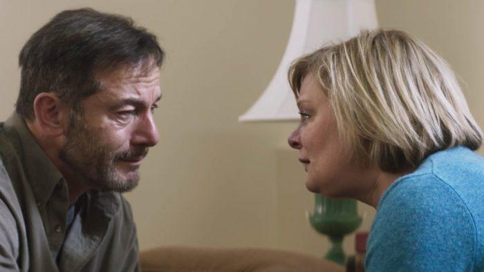 Jay (Jason Isaacs) comforts his grieving wife Gail (Martha Plimpton)