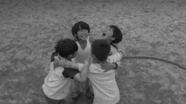 Young boys dance arm in arms in black and white after finish a round of the Squid Game