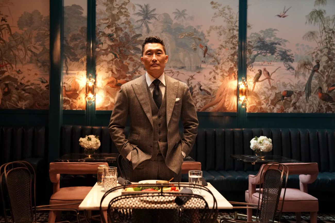 Daniel stands behind a table in a nice restaurant in The Premise season finale